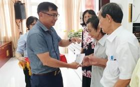 郡越南祖國陣線委員會副主席陳南德向高齡長者贈送禮物。