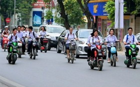 學生騎電動車,但不戴安全帽。