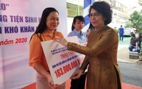 市越南祖國陣線委員會主席蘇氏碧珠向各郡縣頒贈建設溫情屋、情義屋的經費。