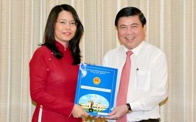 新任市旅遊廳長阮氏映華(左)從市人委會主席阮成鋒手中接過人事委任《決定》。
