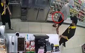 一名戴著口罩的男子手持刀具威脅便利店裡的2名員工交出錢來。(圖源:監控視頻截圖)