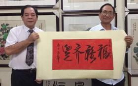 人民藝人張漢明(右)送墨寶給高維山副主席。