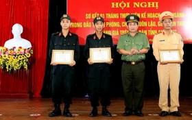 安江省公安廳廳長丁文處大校(右二)向3 名英勇營救遇險船員的水路警察頒贈獎狀。