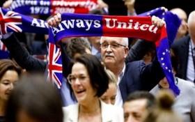"""當地時間1月29日,歐洲議會批准""""脫歐""""協議。圖為投票結束後,在場議員高舉""""永遠團結""""旗幟。(圖源:互聯網)"""