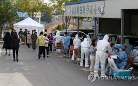 韓國市政府工作人員排隊等候接受新冠病毒檢測。(圖源:韓聯社)