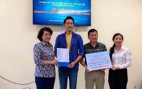 阮飛雄歌星與平西市場越華商販將善款交給市越南祖國陣線委員會領導。