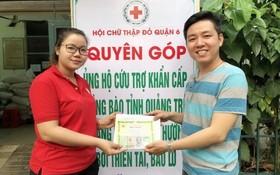 曾廣健(右)把籌到的善款移交給第六郡紅十字會會計黎氏紅雲。