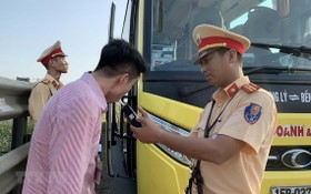 交警在給一名客車司機進行呼氣式酒精測試。(圖源:越通社)