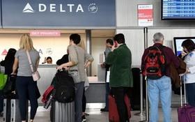乘客在達美航空櫃檯辦理登機手續。(圖源:Getty Images)