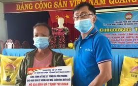 第五郡越南祖國陣線委員會副主席陳南德向貧戶贈送建溫情屋經費。