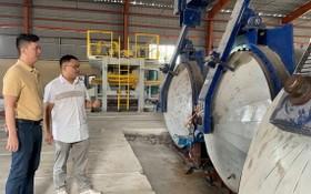 馬順通(左)與中國專家何明祥在研究新引進的無石棉矽酸鈣 板生產線。