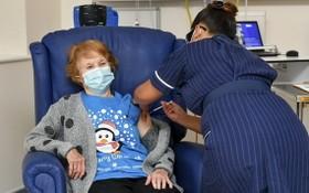 90歲老婦基南(左)接受護士為她注射輝瑞與BioNTech研製的新冠疫苗。(圖源:AP)