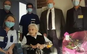 因為疫情的關係,大家在客廳裏都帶著口罩,給老壽星獻了一束鮮花,免了分享蛋糕的節目。(圖源:互聯網)