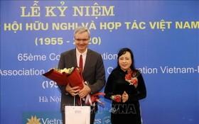 越-法合作與友協主任阮氏金進(右)向法國駐越南大使尼古拉斯‧華納贈送鮮花。(圖源:越通社)