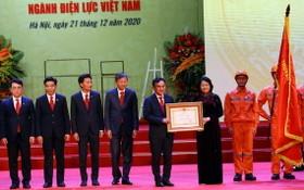 國家副主席鄧氏玉盛(右三)向越南電力部門頒授旗幟和革新時期勞動英雄稱號。(圖源:VTV)