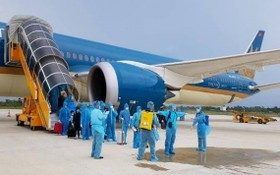 圖為從疫區國撤回的越南公民下機時接受噴灑消毒。(圖源:T.L)