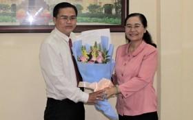 高清平同志(左)從市人民議會主席阮氏麗手中接過人事委任《決定》和祝賀鮮花。(圖源:元宇)