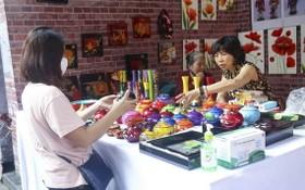 一名遊客在選購磨漆手工藝品。(圖源:俊德)