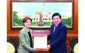 市人委會主席阮成鋒(右)向新加坡駐越南特命全權大使凱瑟琳‧王贈送紀念品。(圖源:越勇)