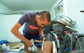 吳戰勝在租房裡修理舊自行車。
