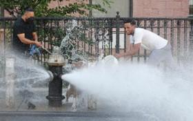 當地時間2020年7月27日,兩名青年在紐約布魯克林街道上噴水的消防栓前嬉水消暑。(圖源:Getty Images)