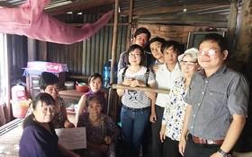 阮復興教師(右一)帶領學生到一個貧困家庭送禮品。