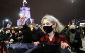 在波蘭首都華沙,數以千計的女性和年輕人當地時間週三晚不顧防疫限制,點燃火炬、揮舞支持性小眾權利的彩虹旗和與手持標語牌,上街抗議墮胎法令。(圖源:路透社)