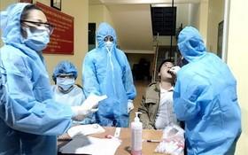 防疫工作人員向新冠肺炎疑似患者進行深喉拭子取樣測試。(圖源:越通社)
