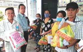 玻璃業團主席李國強(左一)和熱心廠商楊慶文(左二)向團員派發禮物。