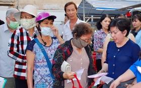 黎美淵向(右一)越華同胞贈送口罩和防疫手冊。