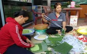 裴氏邊(右)在春節前夕給貧困工人送肉粽過新年。