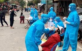 防疫工作人員對海陽省金城縣金蓮鄉的疫區居民進行鼻拭子取樣測試。(圖源:T. Thắng)