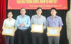 永隆省委宣教處主任阮孝義(左二)向宣教工作方面取得優秀成績的集體頒發獎狀。(圖源:N.H)
