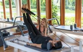 遊客在先進的健身機上練習普拉提。