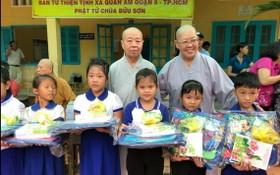 振淨法師(後排右一)向清貧小學生派發禮物。