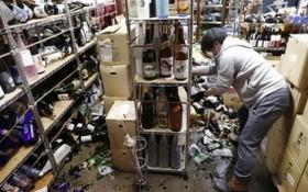 當地時間2月13日,日本福島縣,地震過後,一名員工清理店舖內破碎的酒瓶。(圖源:路透社)