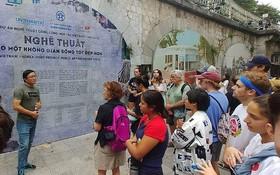 藝術家阮世山向美國遊客介紹馮興壁畫街。