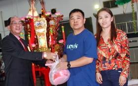 """該廟理事長黃偉峰(左)向鄧奕波先生伉儷(右)轉交""""觀音蓮花寶燈""""。"""