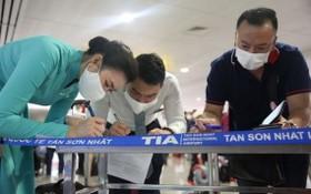 乘客在新山一機場填寫健康申報表。(圖源:垂楊)
