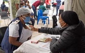 3月2日,工作人員在南非約翰內斯堡的一家醫院為前來接種新冠疫苗的醫護人員測量體溫。(圖源:新華社)