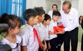 政府常務副總理張和平(右一)向武鴻山殘疾兒童撫養中心的小朋友們贈送禮物。(圖源:阮玉)