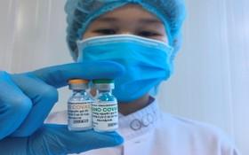 一名醫務人員拿著兩小瓶國產新冠疫苗。(圖源:冰心)