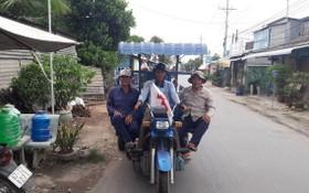 陳文懷(右)與三輪車隊成員們在去砍柴的途中。