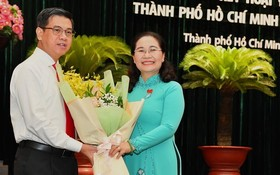 市人民議會主席阮氏麗(右)向阮文勇同志(左)贈送鮮花表示祝賀。