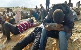 錄像片段顯示了該沉船事故中的數十名倖存者,他們坐在al-Khums海岸的沙灘上。(圖源:AFP)