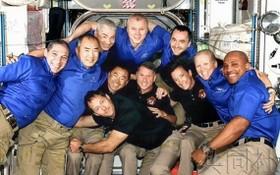 新到站的 4 名宇航員(黑衣者)同空間站內的宇航員們一起合影。(圖源:共同社)