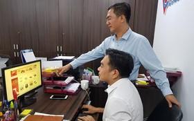 """陳輝強(站)與同事一起查看在""""堤岸線上集市""""上商品。"""