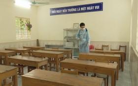 防疫工作人員在為教室課桌椅及講台進行消毒。(圖源:陶芳)