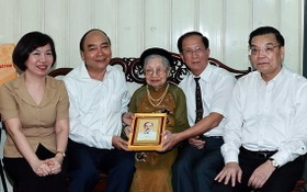 國家主席阮春福(左二)與河內市領導一同探望阮泰來烈士母親阮士秀並贈送禮物。(圖源:統一)