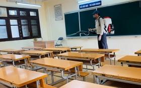 學生提早放暑假,校方安排專人為課室進行噴灑消毒。(示意圖源:互聯網)